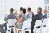 Smiling business team applauding during conference