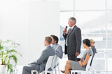 Businessman talking in microphone during conference