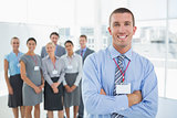 Businessman smiling at camera with team behind him
