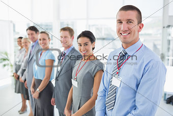 Business team standing in row and smiling at camera