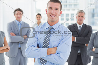 Smiling business team standing with arms crossed