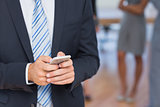 Businessman texting with colleagues behind him
