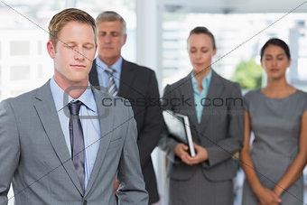Business team meditating eyes closed
