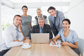 Smiling business team working together on laptop