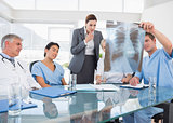 Team of doctors and businesswoman examining xray