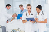Doctors looking at clipboard while theirs colleagues speaks with patient