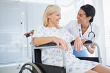 Happy doctor smiling at her patient in wheelchair