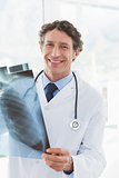 Happy doctor holding X-ray and smiling at camera