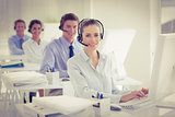 Business team working on computers and wearing headsets