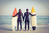 Couple in wetsuits with surfboard on a sunny day