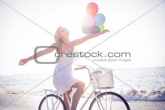 Beautiful blonde on bike ride holding balloons