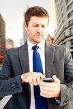 Composite image of businessman sending a text message