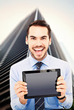 Composite image of happy businessman showing his tablet pc
