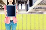 Composite image of elegant brunette using tablet