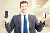 Composite image of businessman holding two smart phones
