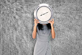 Composite image of businesswoman holding clock