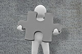 Composite image of white character holding jigsaw piece