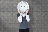 Composite image of woman holding clock in front of her head