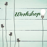Workshop against light bulbs on wooden background