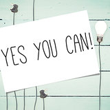 Yes you can! against light bulbs on wooden background