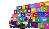 Composite image of mature businessman sitting using tablet