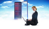 Composite image of redhead businesswoman using her laptop
