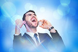 Composite image of cheering businessman in suit on the phone