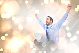 Composite image of excited cheering businessman sitting using his laptop