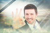 Composite image of businessman smiling and making ok sign