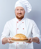 Head-cook holding freshly baked bread