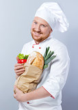 Head-cook smiling and holding package with fresh food