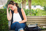 Depressed Young Woman Sitting on Bench at Park