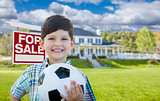 Boy Holding Ball In Front of House and Sale Sign