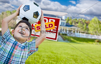 Boy Holding Ball In Front of House and Sold Sign