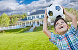 Smiling Young Boy Holding Soccer Ball In Front of House