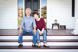 Senior Chinese Couple Sitting on Front Steps of Their House
