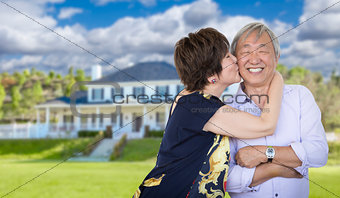 Affectionate Senior Chinese Couple In Front of Beautiful House