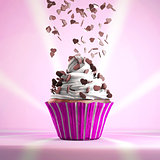 Delicious cupcake with chocolate hearts sprinkled on a whipped cream.