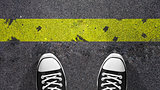 Cross the yellow line ? Concept illustration showing shoes in front of a yellow line.