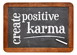 create positive karma - text on blackboard