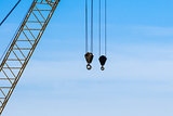Pair of industrial crane hoists on cables near truss.
