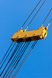 Large yellow pulley and cable assembly on blue sky.