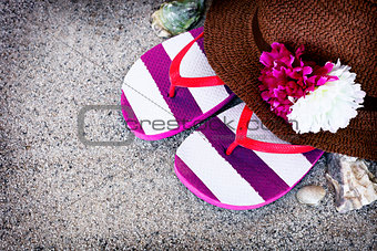 Beach background with straw hat and flip flops