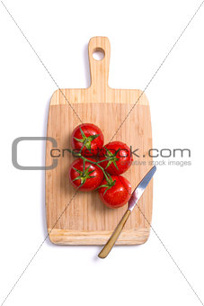 Top view of fresh tomatoes and a knife on chopping board