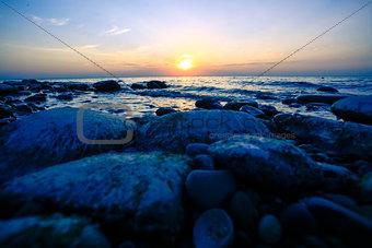 Amazing Sunset over the coast of pebble ocean