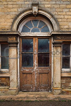 Old decaying wooden double doors in a stone archway