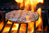 Juicy beef burger sizzling over hot flames on the barbecue