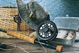 Hat and fly fishing gear on table near the water