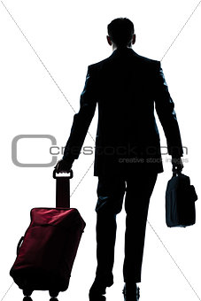 business traveler man walking with suitcase  rear view silhouett