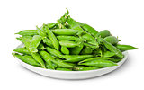 Big pile of green peas in pods on white plate